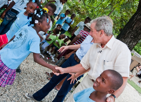 Former President George W. Bush visits with schoolchildren at GHESKIO.