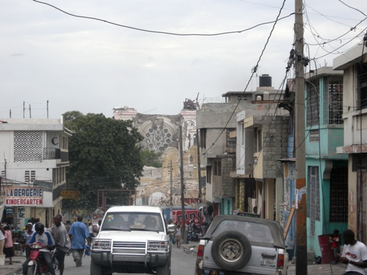 Port-au-Prince's collapsed cathedral can be seen in the background.