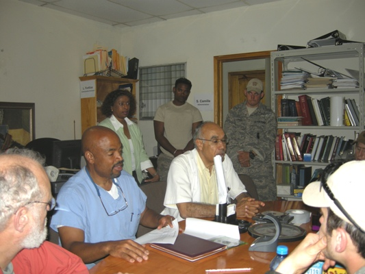 Dr. Henri Ford (left), Dr. Jean Pape (right) and others in a staff meeting.