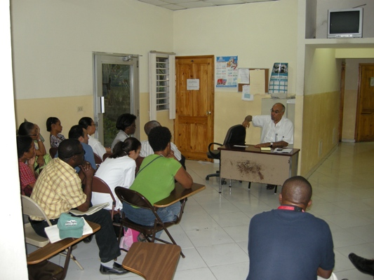 Dr. Pape holds an evening meeting with GHESKIO staff.
