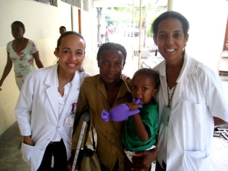 Eclane and her son Kervins, separated after the earthquake, are finally reunited with the help of GHESKIO staff, Vanessa Rouzier, MD (left) and Claudia Riche, RN