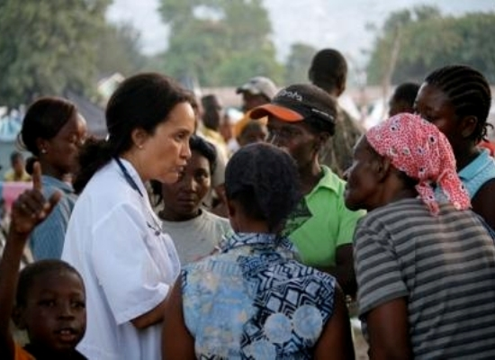 Dr. Marie-Marcelle Deschamps speaks with women in the refugee camp
