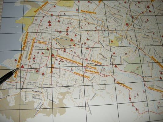 Map of downtown Port-au-Prince; triangles represent refugee camps and their size correlates with the size of the camps. The pen points to GHESKIO's camp, which is among the biggest.