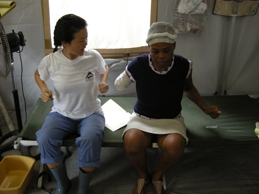 A NYPH volunteer helps a patient exercise her shoulder.
